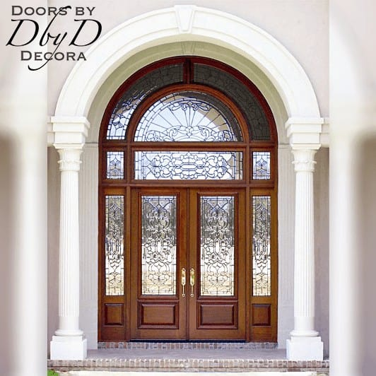 A beautiful and grand entrance featuring multiple transoms and custom beveled glass.