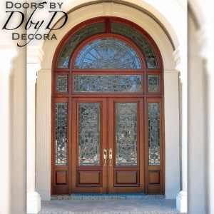 This beautiful entrance features two double custom doors, side lites, and a double transom.