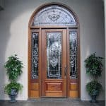 A traditional door, two side lites, and transom with leaded glass.