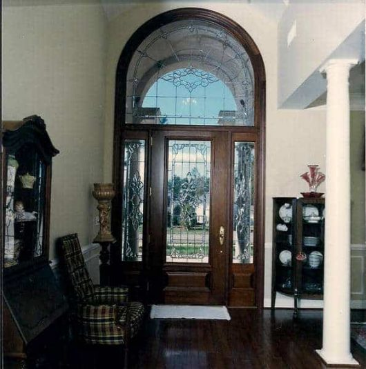 Door, two side lites, and extended leg transom, all featuring leaded glass.