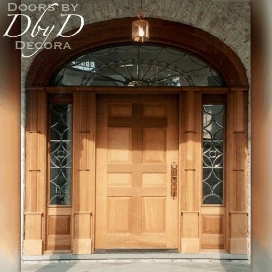 A grand and impressive solid door with leaded glass side lites, elliptical transom, and custom jamb molding.