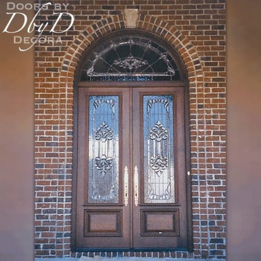 Traditional double doors with a radius transom and custom leaded glass.