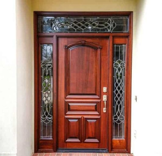 Beautiful solid door surrounded by custom leaded glass in the side lites and transom.