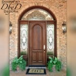 A simple solid door surrounded by two side lies and a transom featuring custom leaded glass.