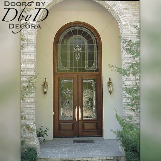 Double doors with an extended leg radius transom featuring leaded glass.