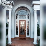 A full lite door with two side lites, a three piece transom, and a radius transom on top. All feature custom leaded glass.
