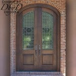 Double elliptical doors with rondel leaded glass.