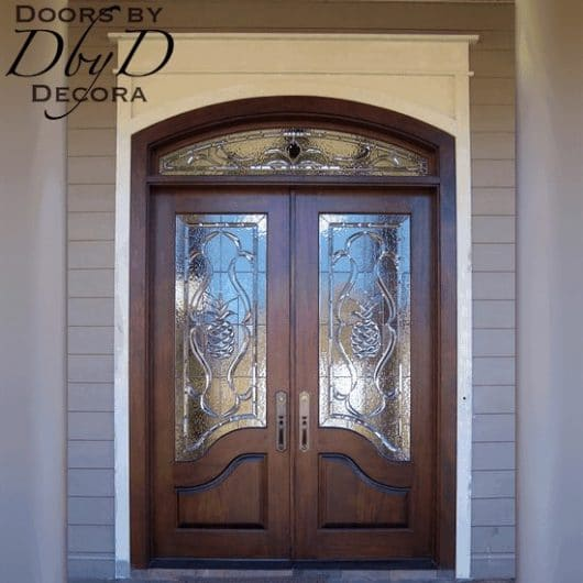 A beautiful pair of double doors and a segment transom with custom leaded glass.