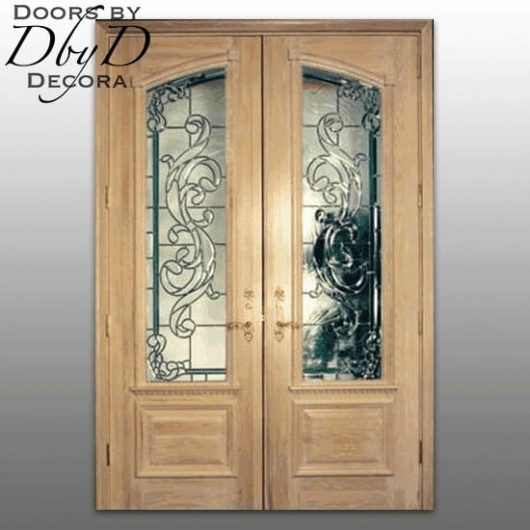 A pair of unfinished double doors with architectural molding and leaded glass.
