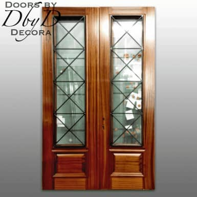 A pair of double doors featuring custom wrought iron grills.