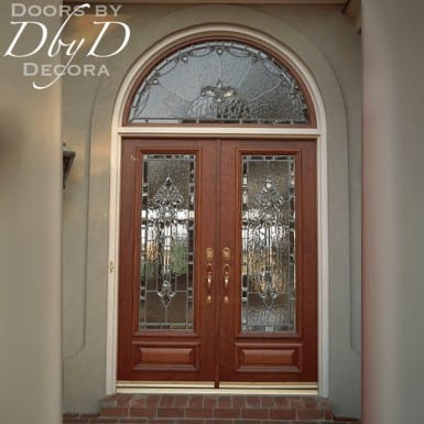 A pair of full lite doors featuring leaded glass and a radius transom.