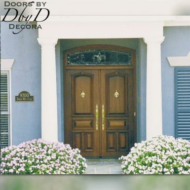 A pair of beautiful double doors with a leaded glass transom above.