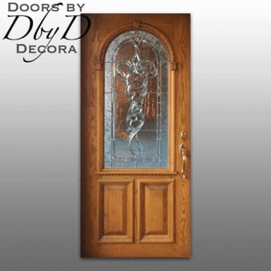 Traditional oak door with architectural molding and leaded glass.