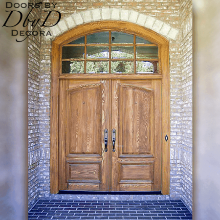 A pair of distressed country french doors with a segment top transom with true divided lites.