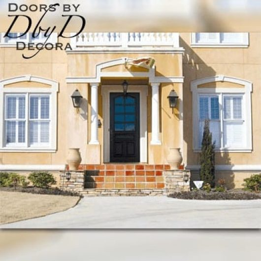 A country french style home featuring a custom door designed and built by Doors by Decora.