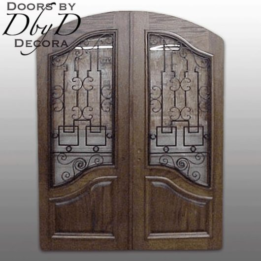 A pair of common segment top country french doors with custom wrought iron grills.
