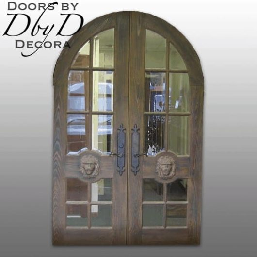 This pair of double radius top doors feature applied carvings of lions.