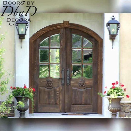 """A pair of distressed """"Lion"""" doors featuring beveled glass."""