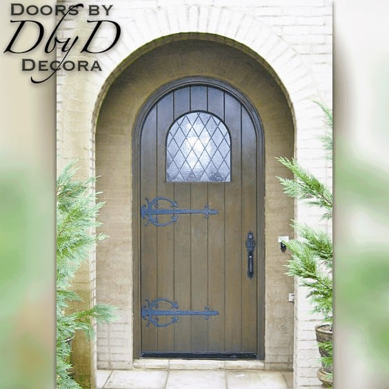 A traditional radius top plank door with strap hinges.