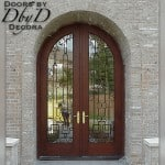 A pair of double radius top doors with a custom wrought iron grill.