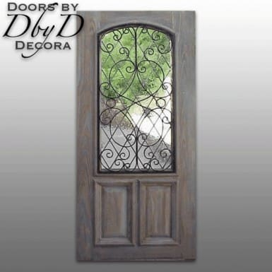 A distressed old world style door with a wrought iron grill over leaded glass.