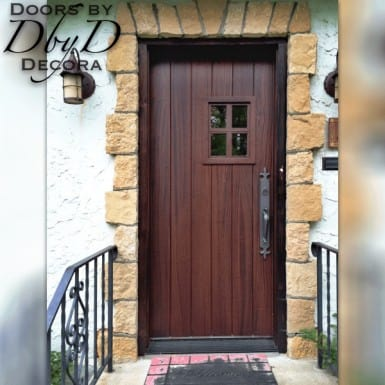 A traditional old world style plank door with a four lite window.