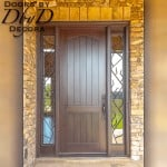This beautiful old world style door features custom wrought iron grills in the site lites.