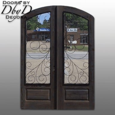 A pair of distressed old world doors featuring custom wrought iron grills.