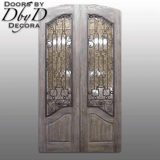 These distressed old world doors feature custom wrought iron grills over glass.