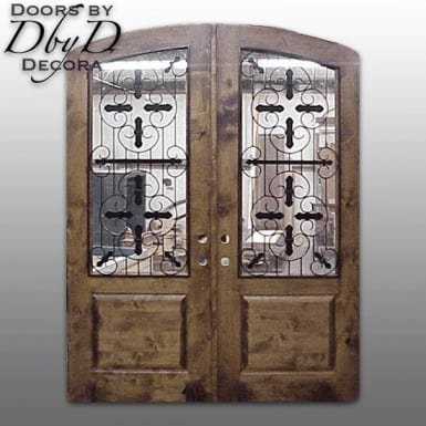 This is a pair of old world style doors with a common segment top and custom wrought iron grills.