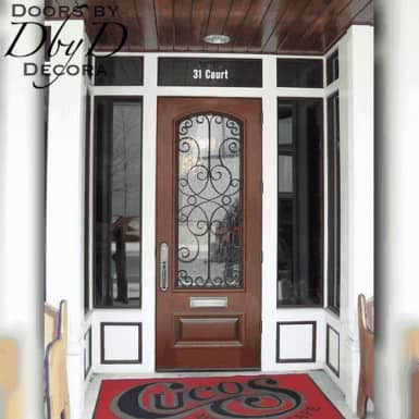 This commercial door features a custom wrought iron grill and a mail slot.