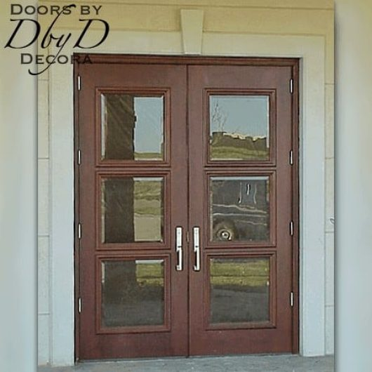 A pair of double commercial doors with beveled glass in place of the wood panels.