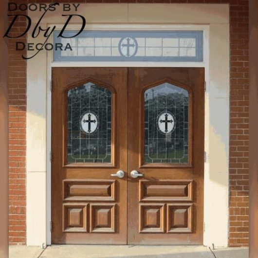 A pair of double church doors featuring custom painted crosses that match the leaded glass in the transom.