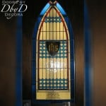 A close up look at the center medallion and dedication plate in this church stained glass window.