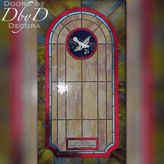 Church stained glass with a hand painted dove medallion and a dedication area.