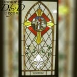 Church stained glass window with hand painted medallion and dedication.