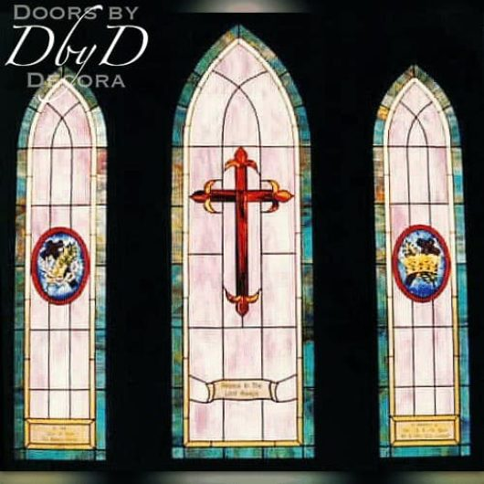 A trio of church stained glass windows with hand painted medallions and dedication areas.