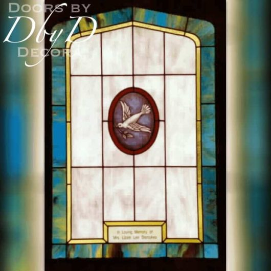 A church stained glass window depicting a dove in a hand painted medallion and a dedication plate.