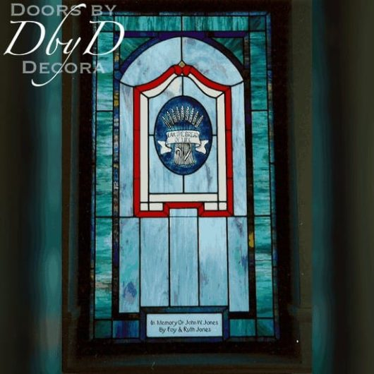 A church stained glass window with a large hand painted medallion and a dedication placque.