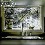A special stained glass window shown over a kitchen sink.