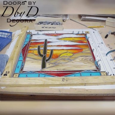A piece of stained glass with a southwest flare shown under construction.