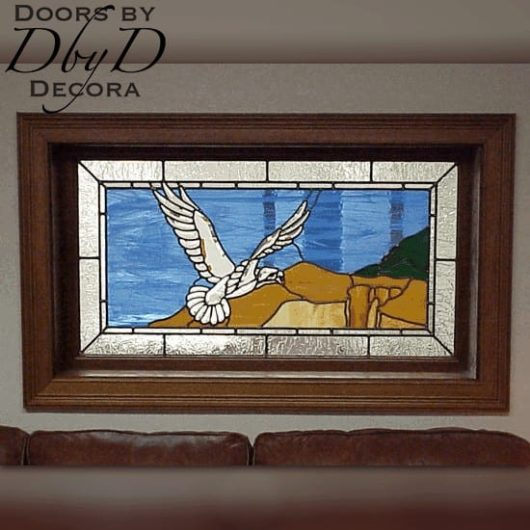 A beautiful beveled eagle soars over land in this custom piece of stained glass.