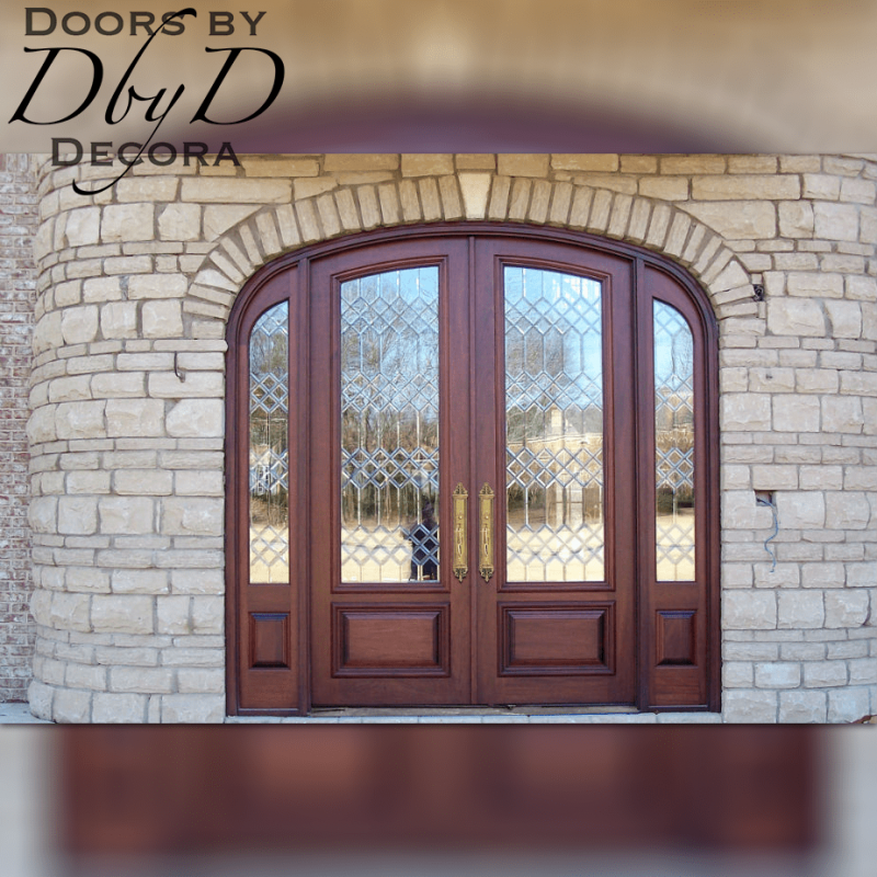 A common elliptical front entrance with double doors and two side lites featuring beautiful custom leaded beveled glass.