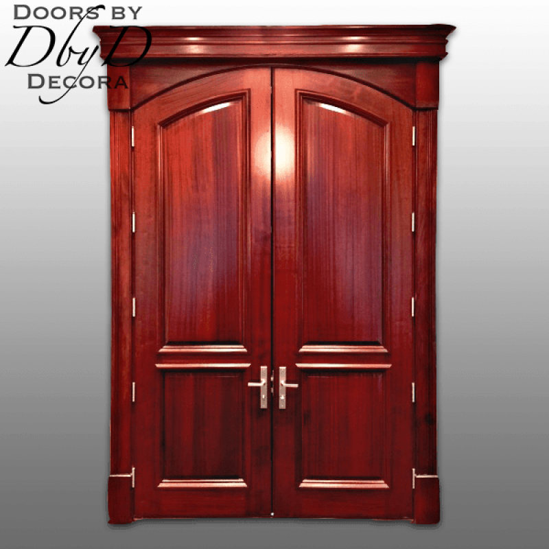 A stunning pair of common segment top doors with custom jamb and molding to accommodate a rectangular opening.