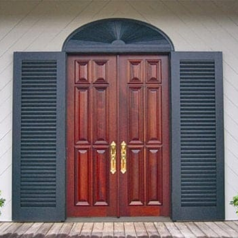 A beautiful narrow pair of solid doors and custom shutters provided by Doors by Decora.