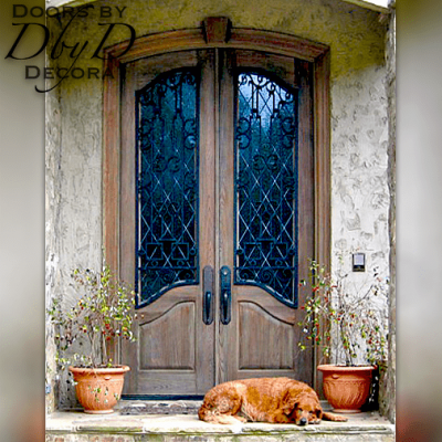 These distressed doors feature custom wrought iron grills over leaded glass.